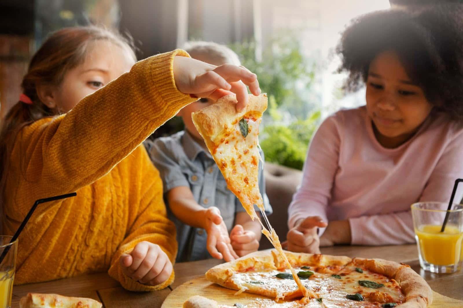 Três crianças, sendo uma menina loira de blusa amarela, um menino de camisa azul e uma menina negra de camisa rosa pegando um pedaço de pizza com queijo derretido.