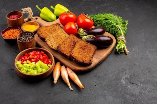 uma mesa com tábua cheia de ingredientes para a caponata de berinjela