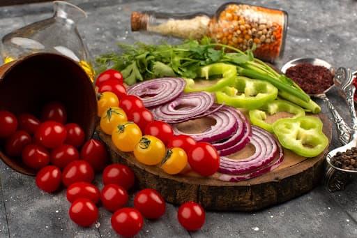 Uma seleção de pimentões e pimentas em cima de uma mesa representando os ingredientes de uma caponata de berinjela