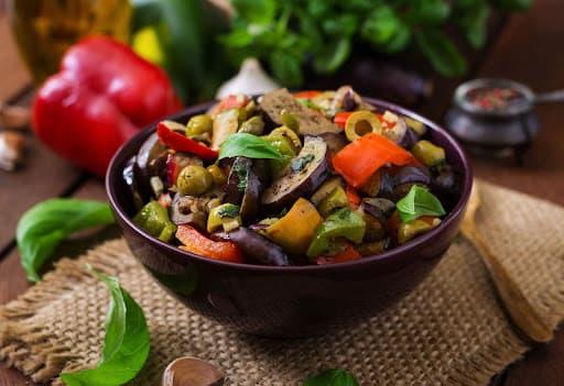 Uma tigela com vários ingredientes da caponata de berinjela