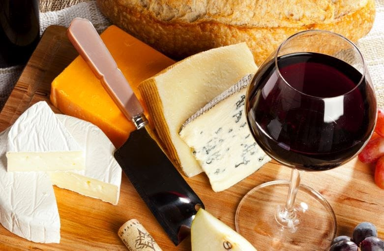 mesa com uma taça de vinho tinto, faca para cortar queijos e pedaços grandes de vários tipos queijos