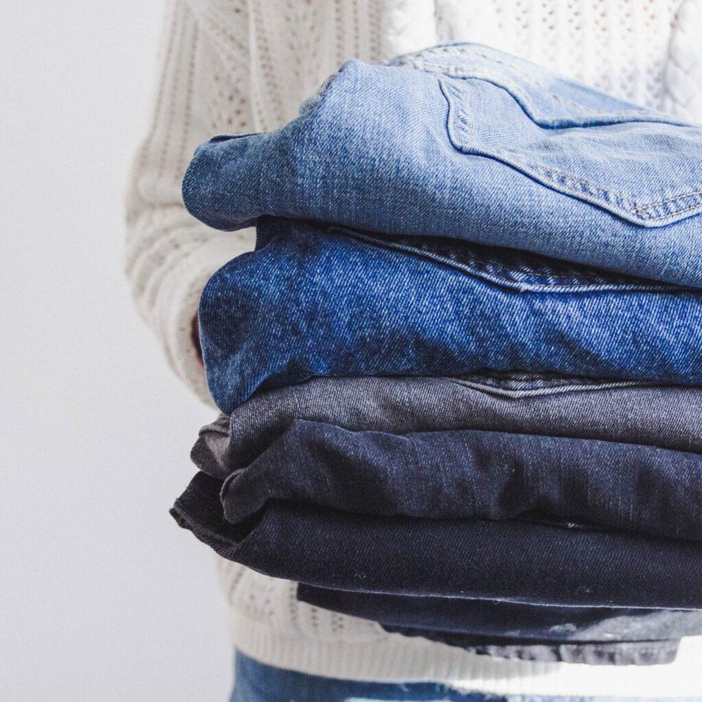 Na imagem uma pessoa carrega 4 calças após entender como tirar mancha de jeans.