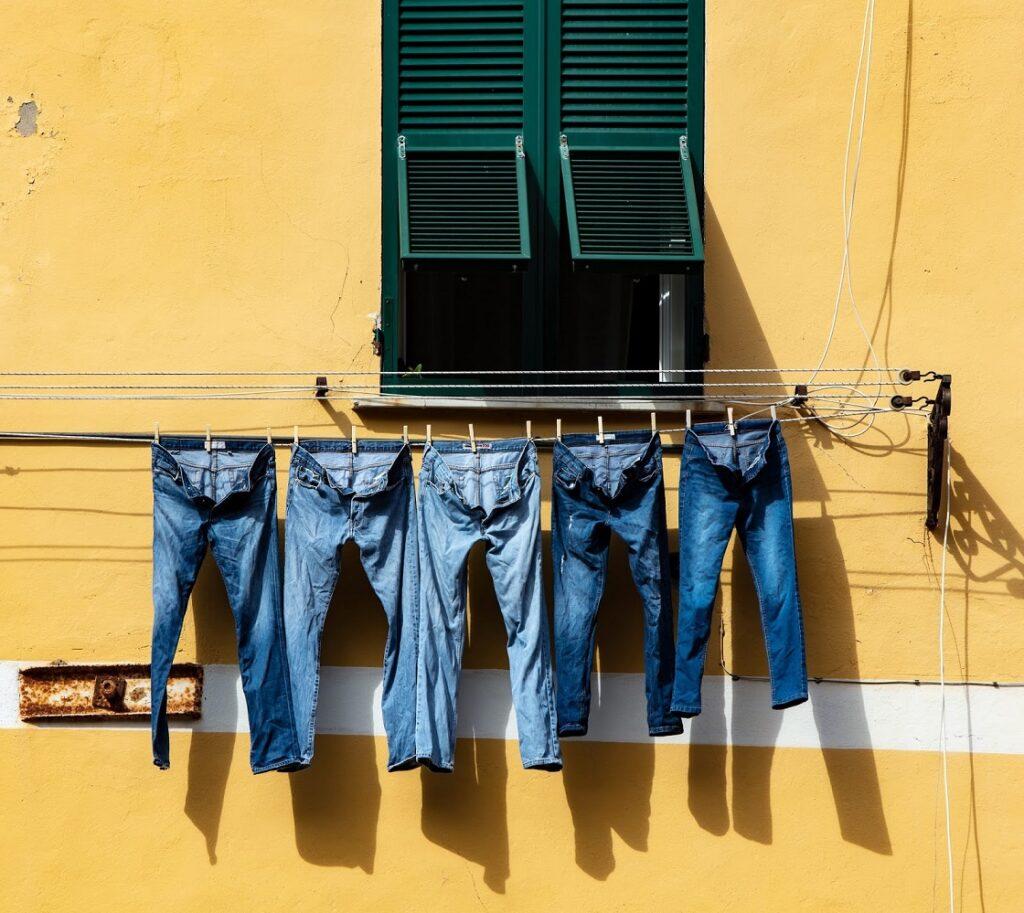 Na imagem, 5 jeans estão estendidos em um varal, com uma parede amarela de fundo, secando ao sol após tirar a mancha de ferrugem do jeans.
