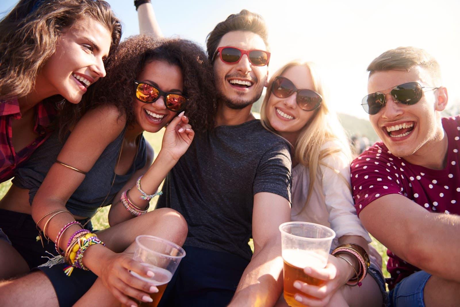 Grupos de amigos tirando selfie com copos de cerveja na mão