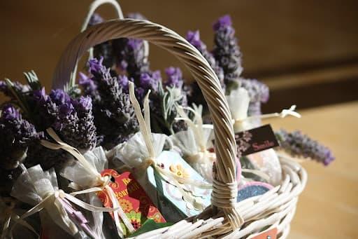 Uma cesta de presente de vime com flores de lavandas e alguns presentes