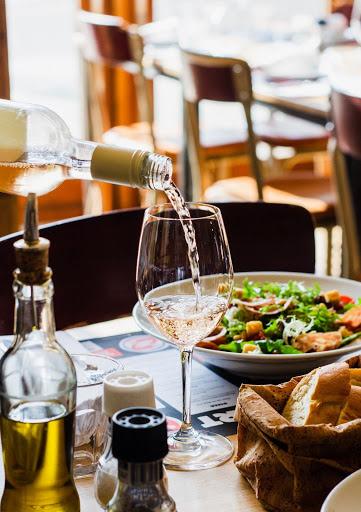 vinho branco sendo servido sobre a mesa