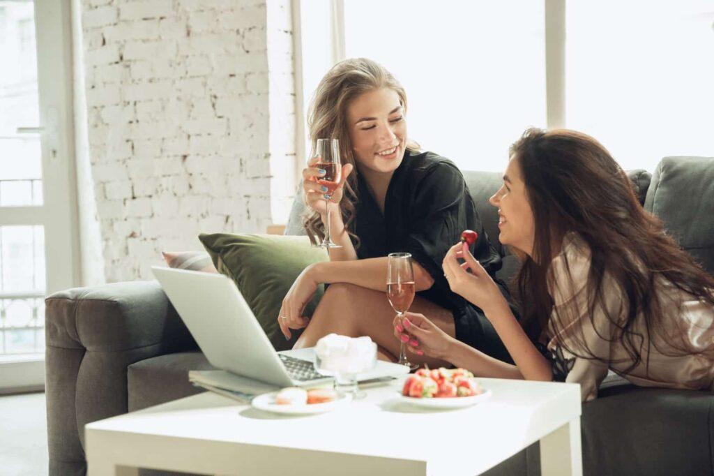 duas mulheres tomando uma taça de vinho