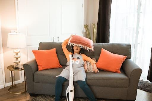 Mulher sentada no sofá com uma almofada laranja na cabeça expressando cansaço por fazer limpeza na casa - para representar a necessidade das dicas de organização