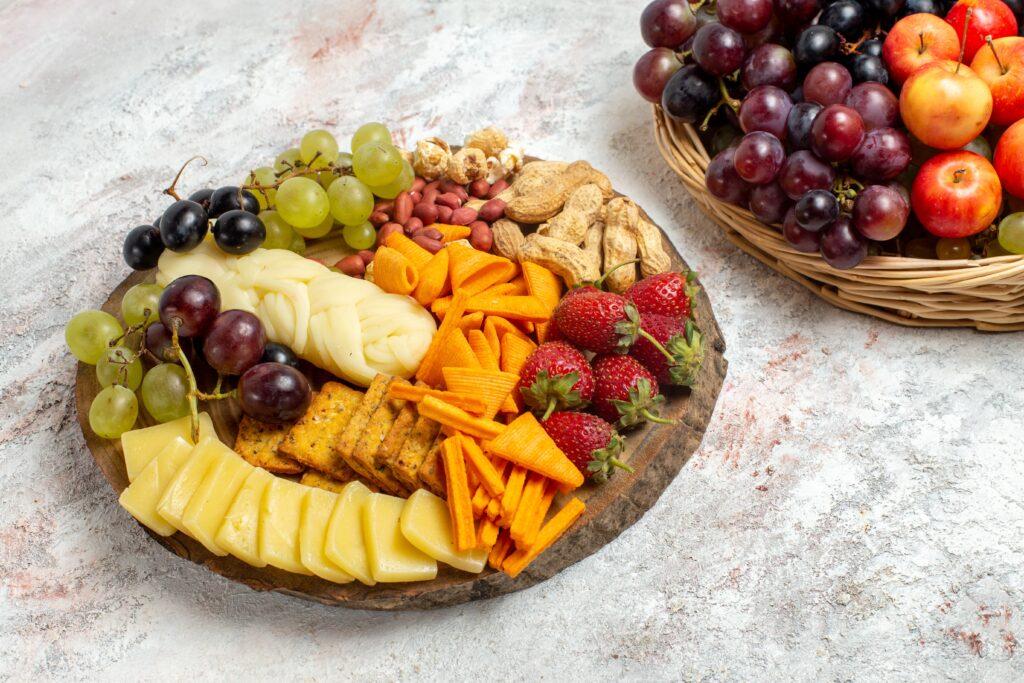 uma tábua de queijos com frutas para representar os petiscos para acompanhar vinho