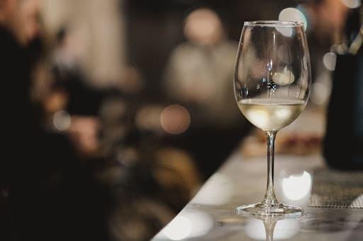 uma taça de vinho branco em cima de um balcão para representar os petiscos para acompanhar vinho