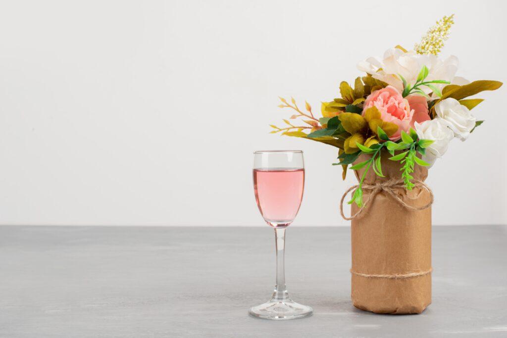 uma taça de vinho rosé em cima de uma bancada com um buquê de flores para representar os petiscos para acompanhar vinho rosé