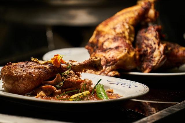Imagem de um frango assado temperado com legumes dividido em dois pratos.