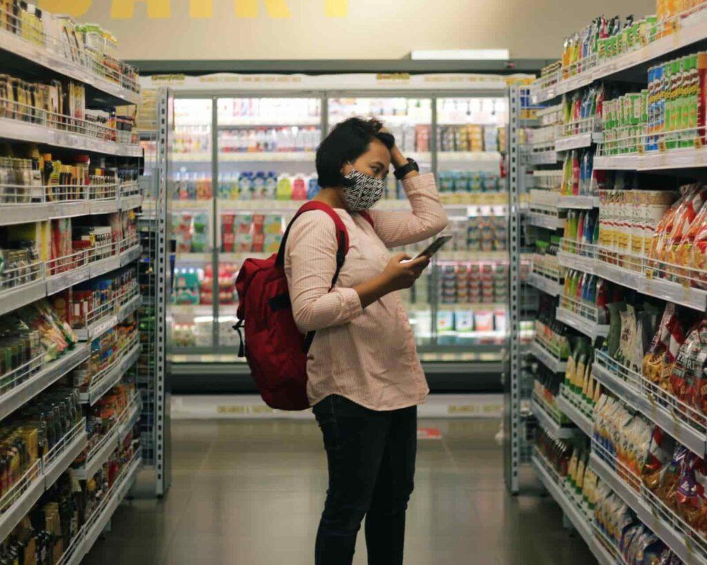 Mulher com o celular na mão, procurando por produtos na gôndula do supermercado