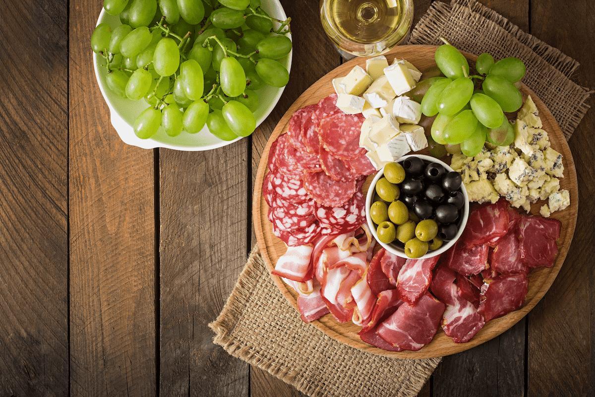 diferente tipos de embutidos em uma tábua acompanhados de uvas verdes