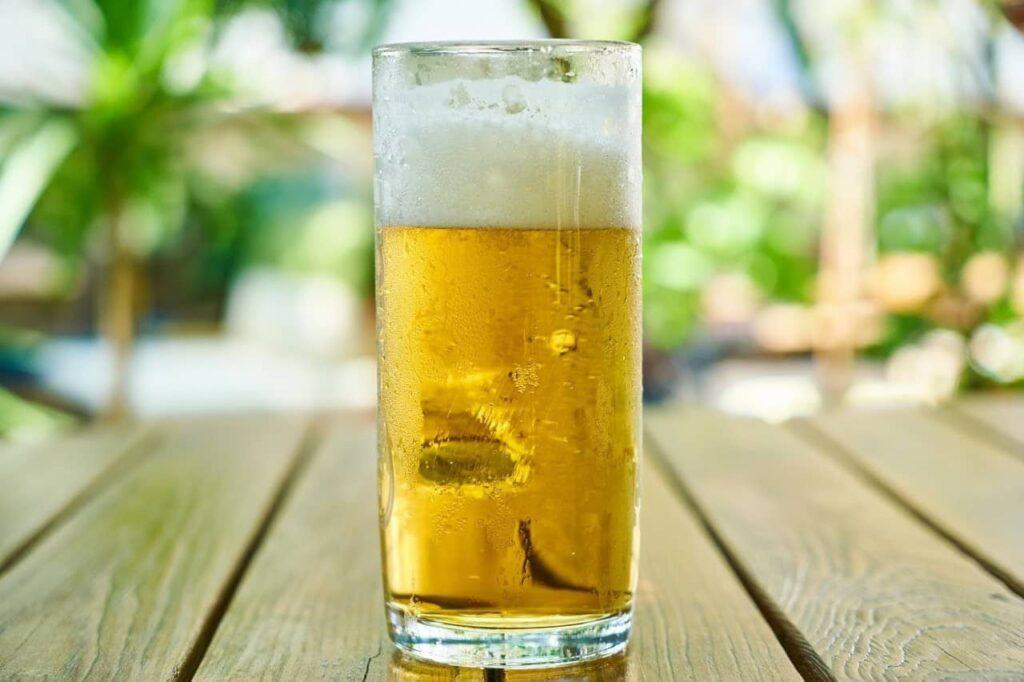 Copo de cerveja bem gelada com um pouco de espuma por cima.
