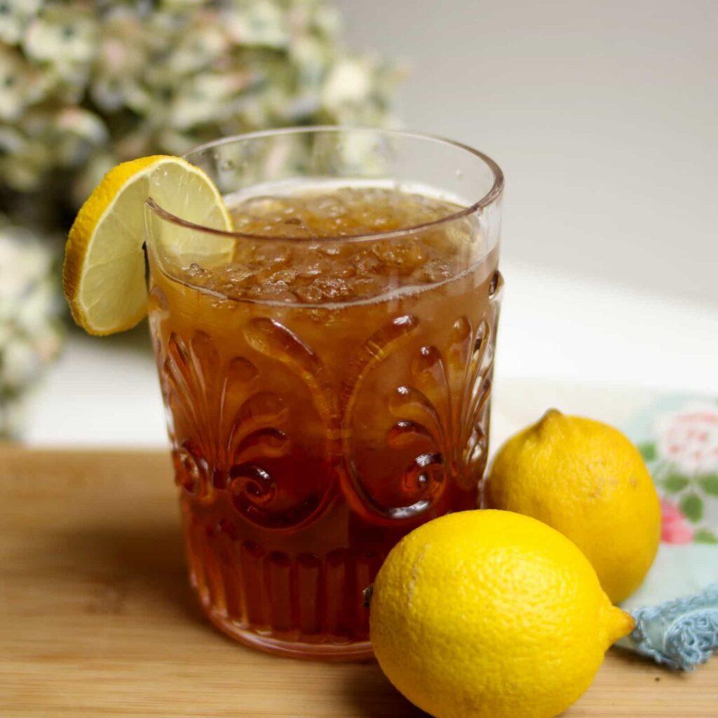 Copo de vidro com chá preto batido com gelo. Ao lado do copo tem 2 limões.