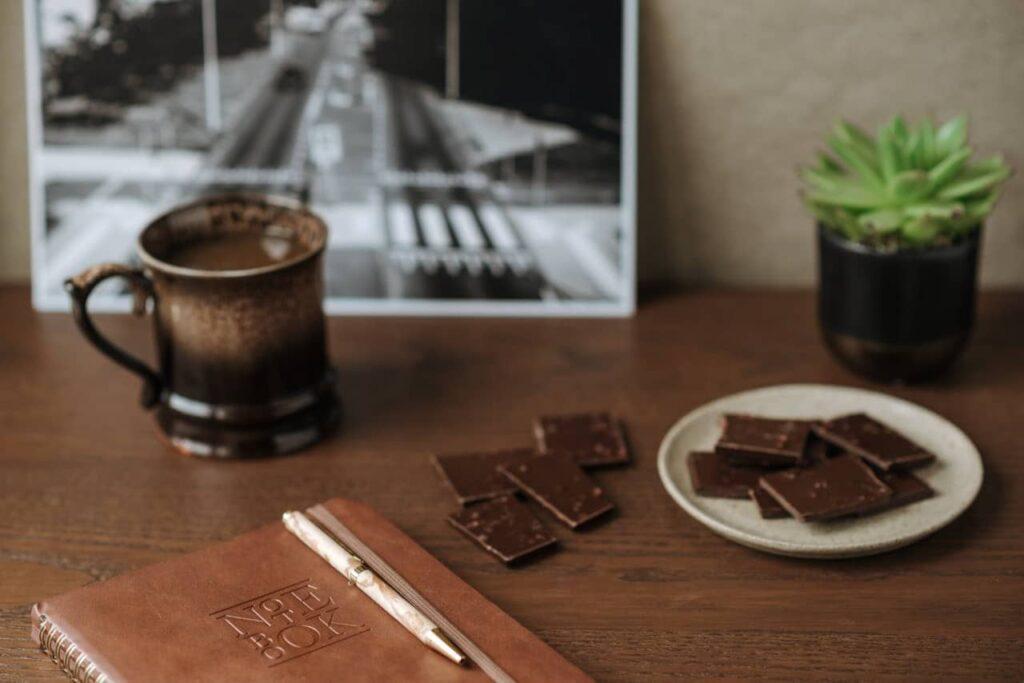 mesa com um copo de chocolate quente e um prato com pedaços de chocolate