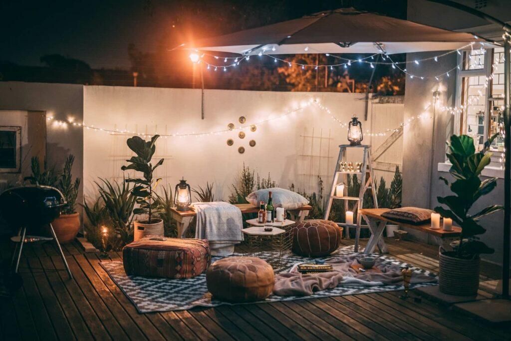 Quintal de uma casa com espaço decorado para um piquenique a noite.