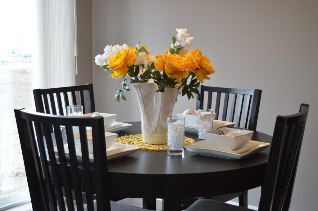 Mesa com 4 lugares montada para um jantar romântico. Flores amarelas ao centro.