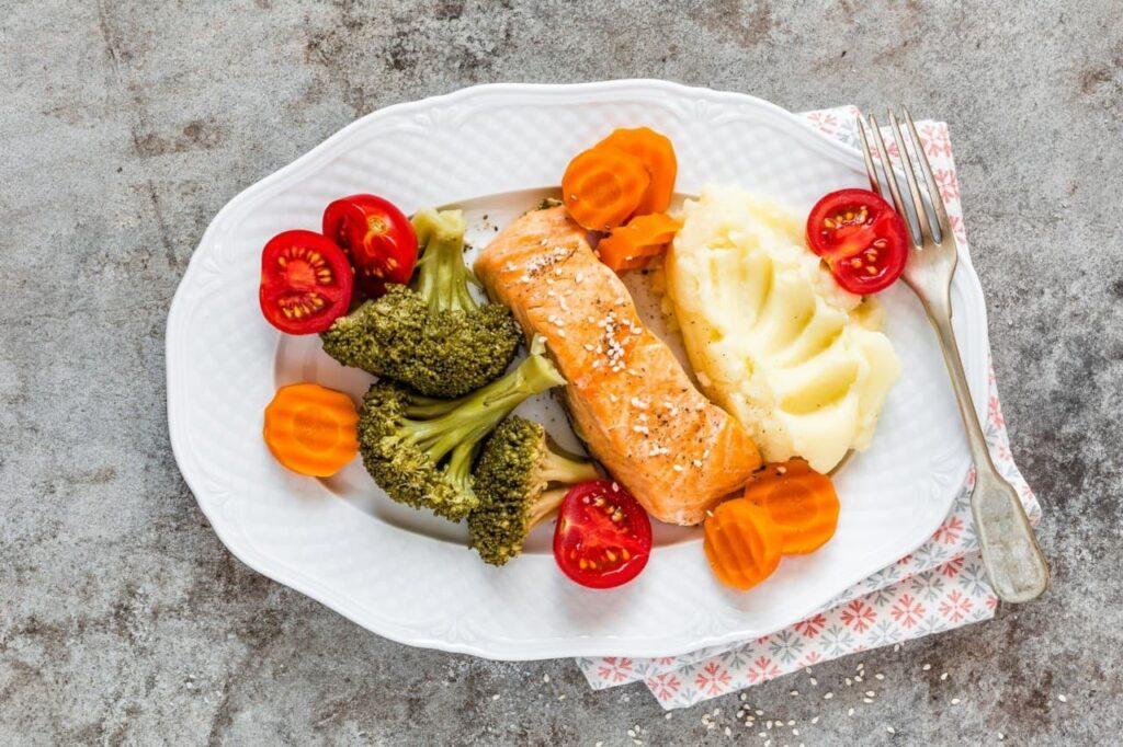 Prato branco com legumes e verduras cortados prontos para alimentação
