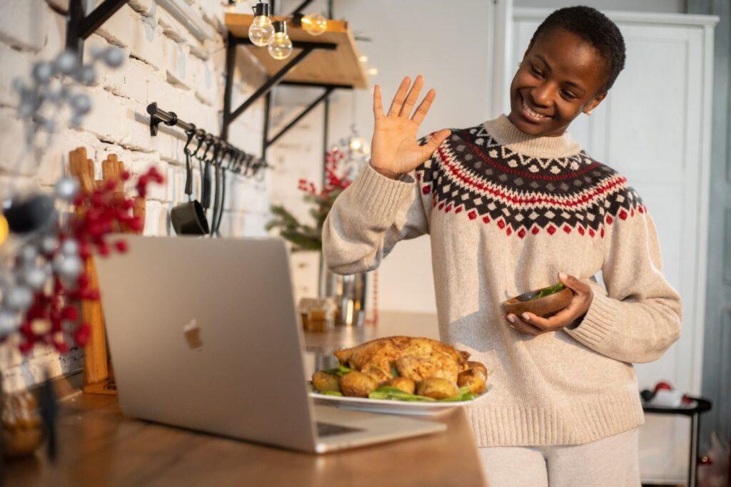 Mulher em frente a um notebook, segurando um prato com petiscos.