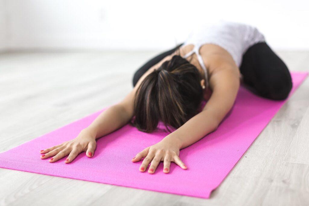 Mulher de bruços no chão alongando as costas em um spa day