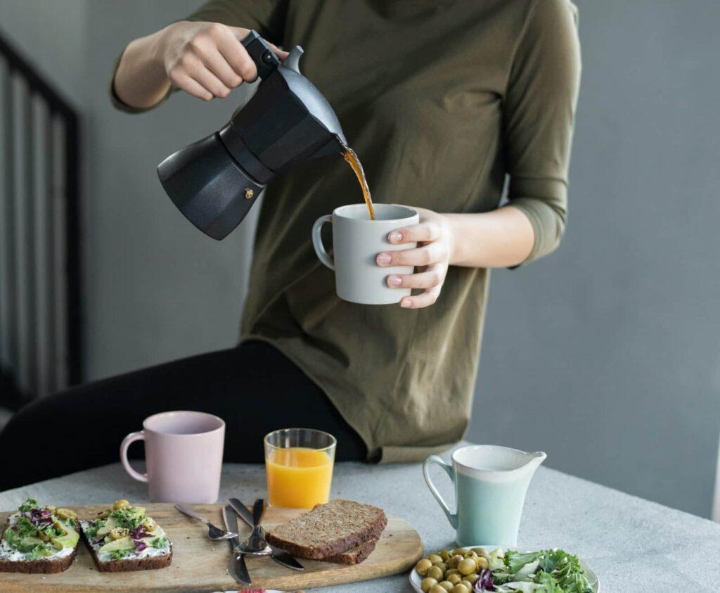Mulher colocando café em sua caneca. Ela está em frente a uma mesa com comidas de café da manhã.
