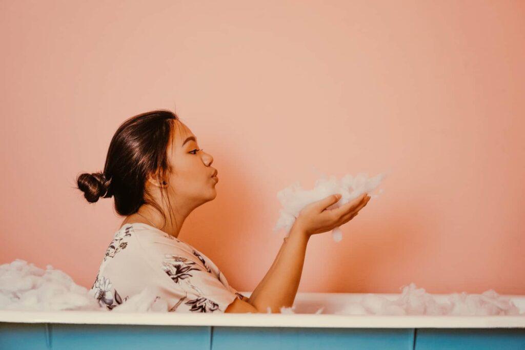 Mulher dentro de uma banheira cheia de espuma.