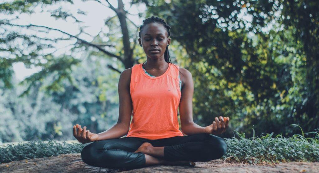 Mulher sentada com as pernas cruzadas, fazendo uma meditação.