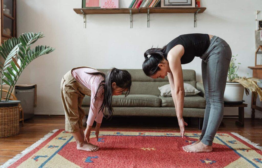 Mãe e filha em uma sala, em pé, alongando as costas uma em frente a outra.