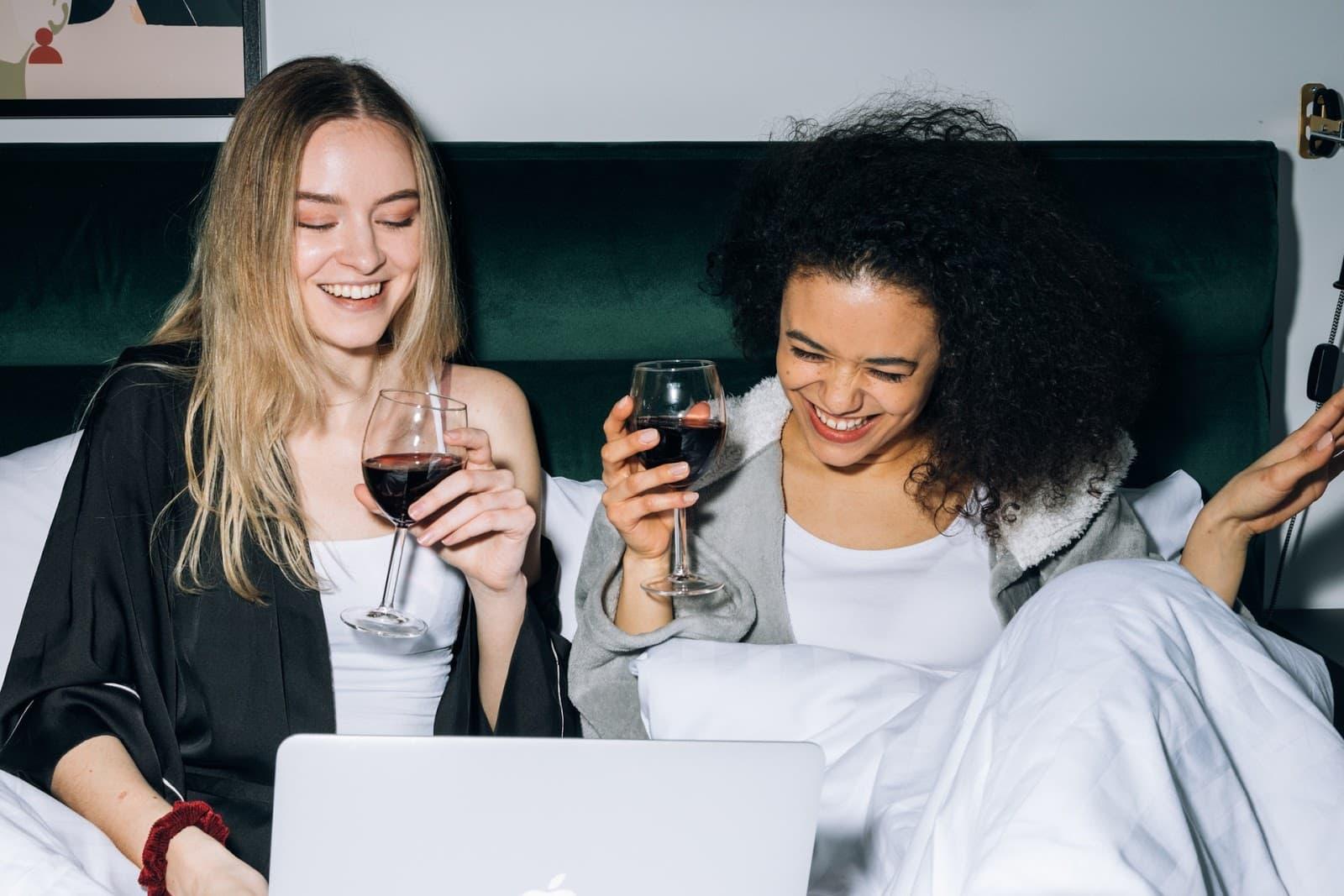 Duas mulheres sorrindo sentadas em uma cama, segurando taças de vinho argentino