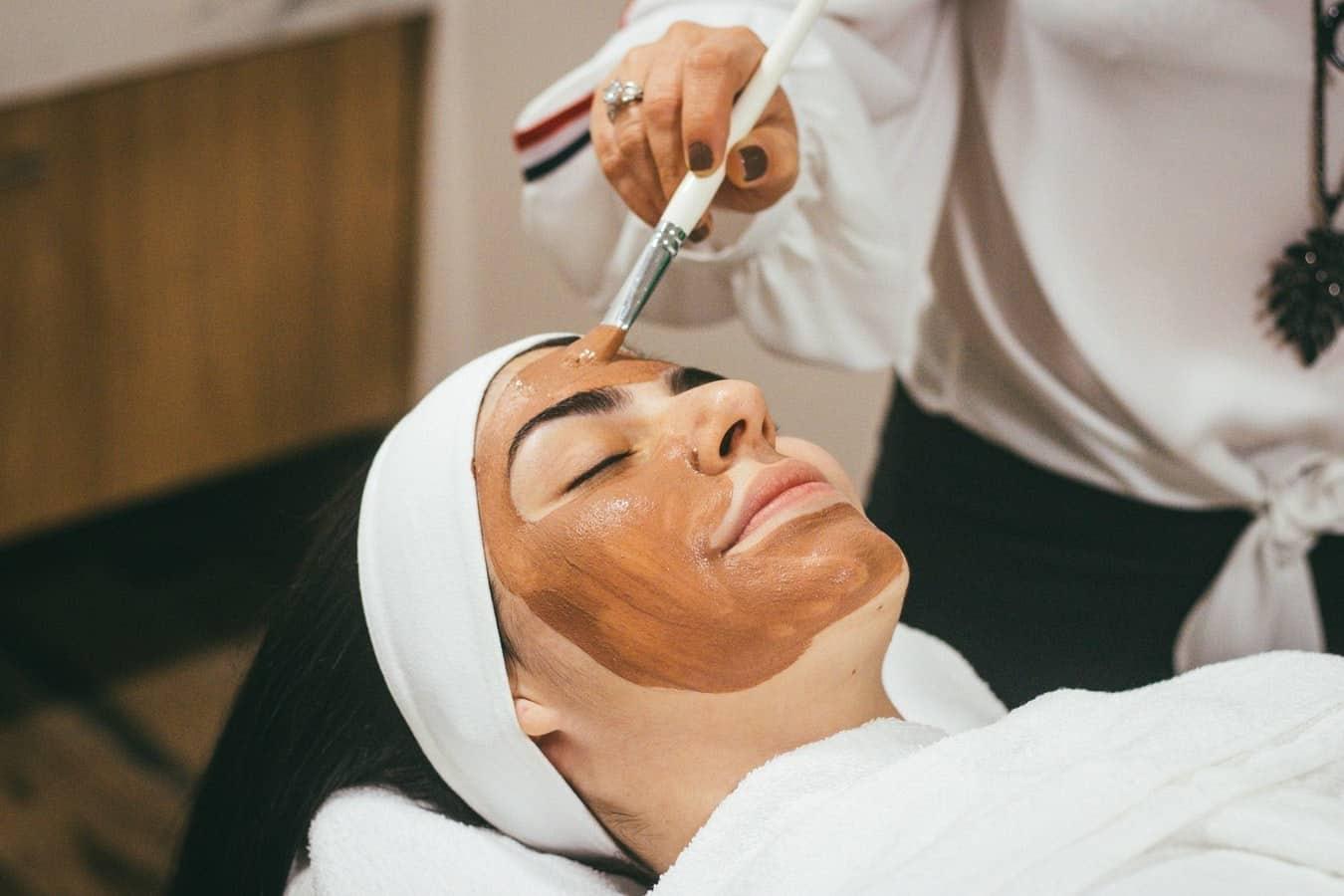 Mulher passando uma máscara de hidratação no rosto de outra mulher.