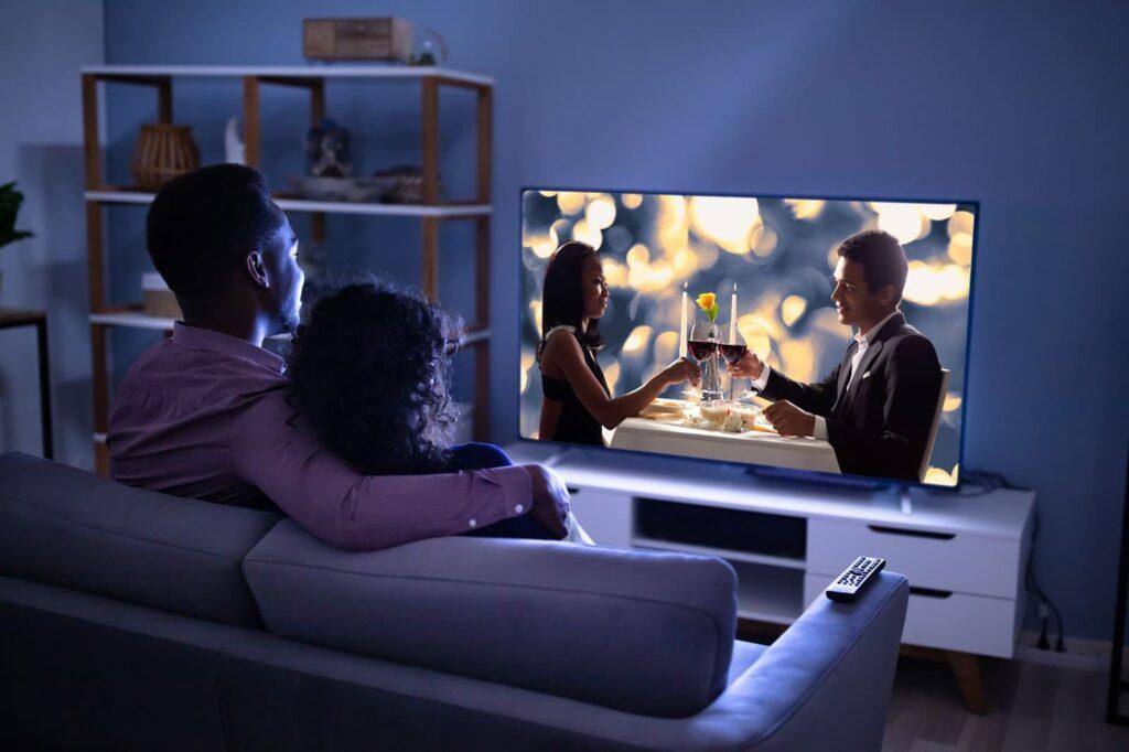 Casal sentado no sofá, fazendo um cinema em casa