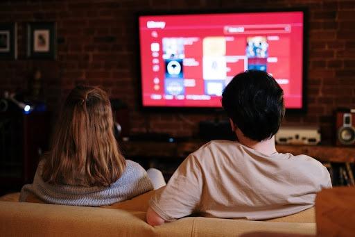 Homem e mulher sentados no sofá, fazendo um cinema em casa