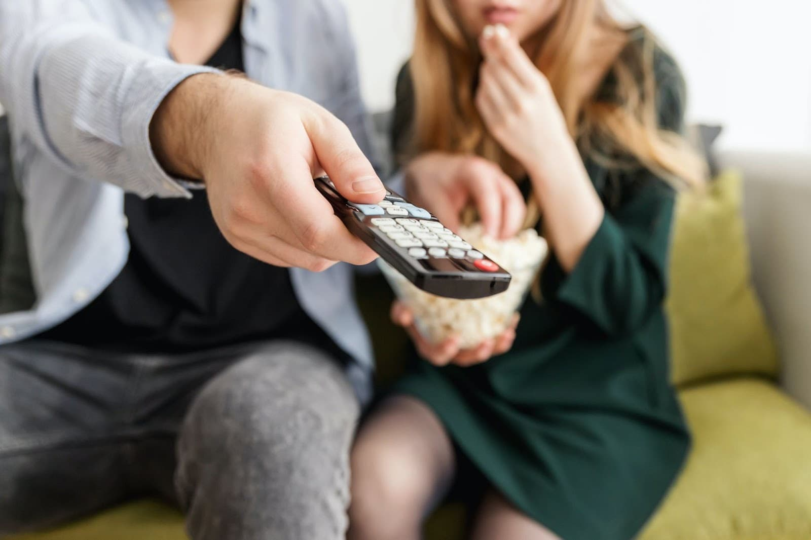 Casal comendo pipoca com um controle de televisão na mão