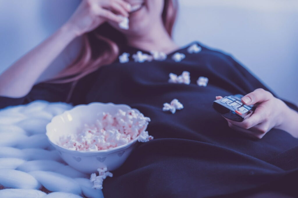 Mulher deitada no sofá, comendo pipoca e fazendo um cinema em casa