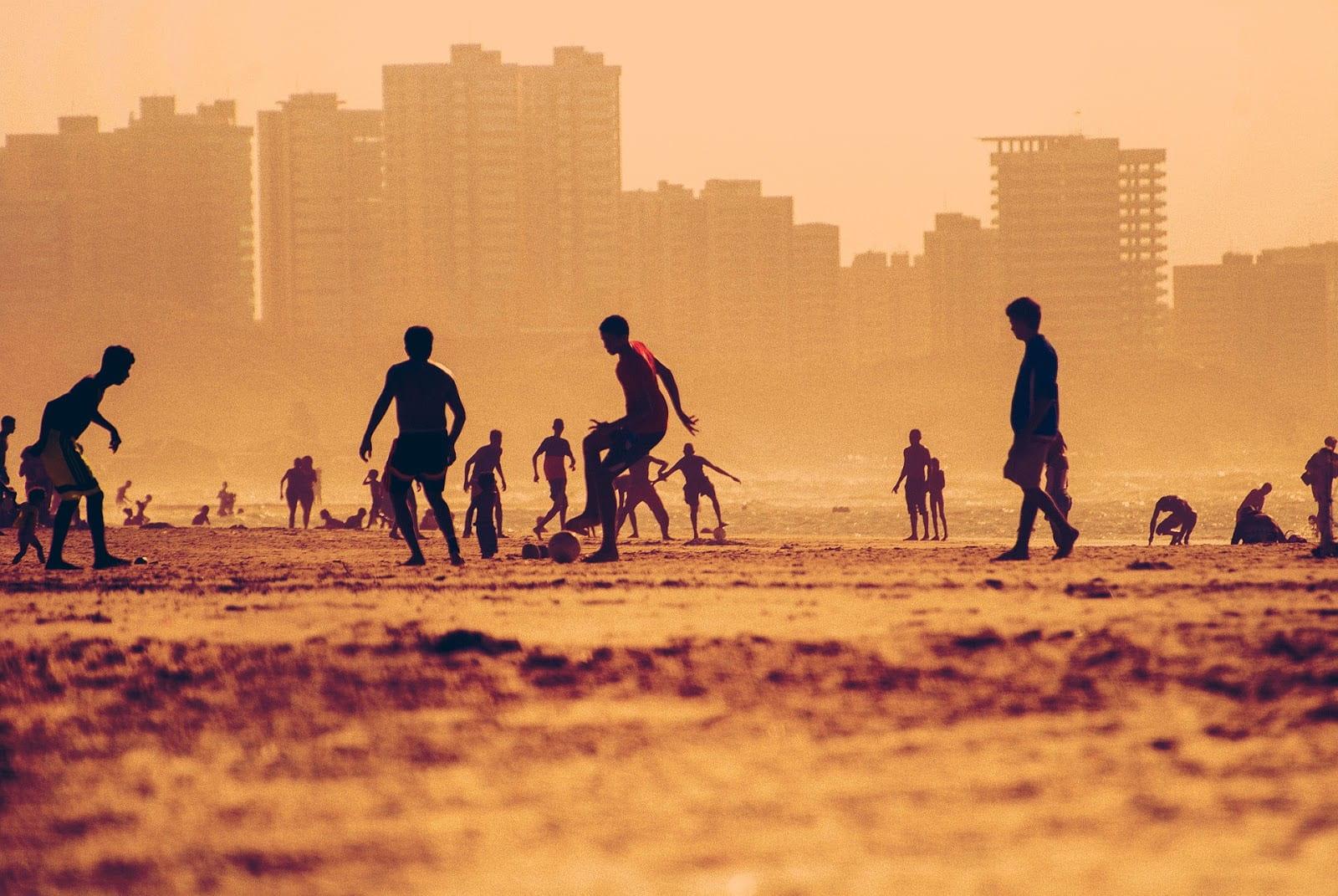Pessoas jogando futebol na praia