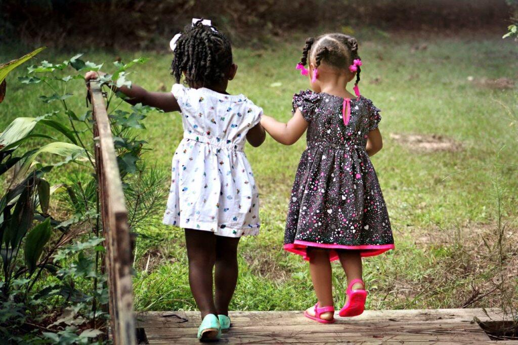 Duas crianças de mão dadas, andando em um quintal.