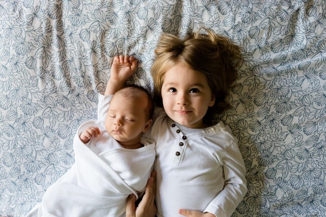 Uma criança e um bebê deitadas na cama