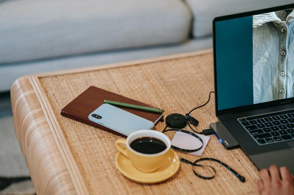 mesa com uma xícara de café preto. Ao lado um notebook e uma caderneta marrom de anotações.