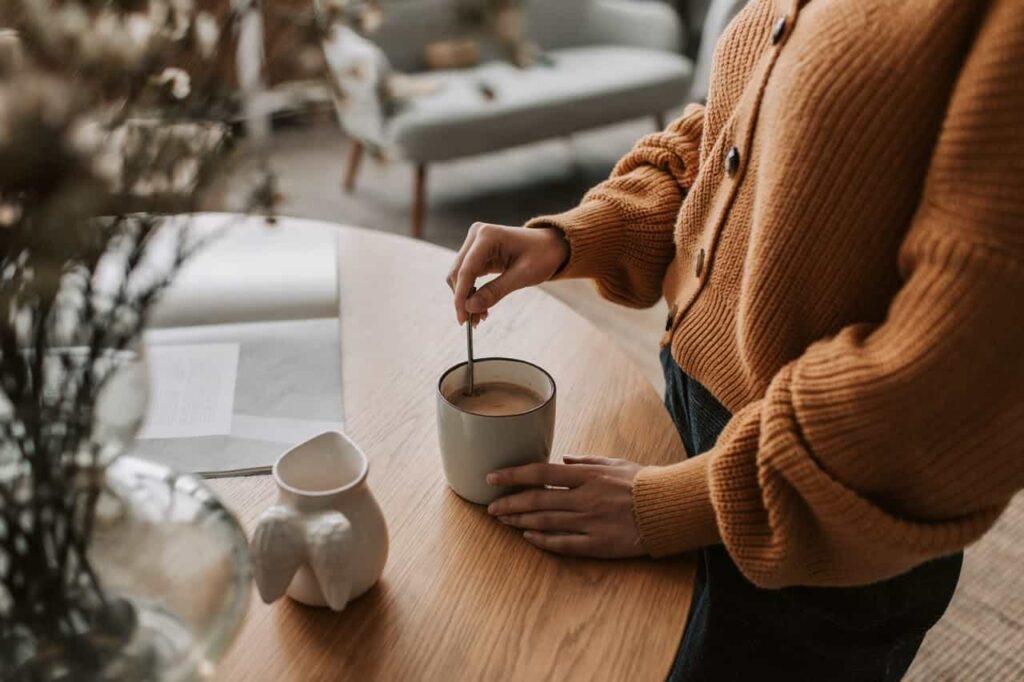 mulher mexendo um copo com cappuccino.