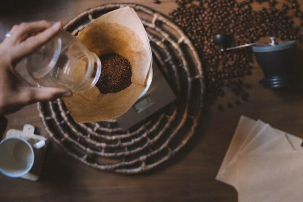 café triturado sendo pesado. Ao lado grãos de cafés enfeitando a mesa.