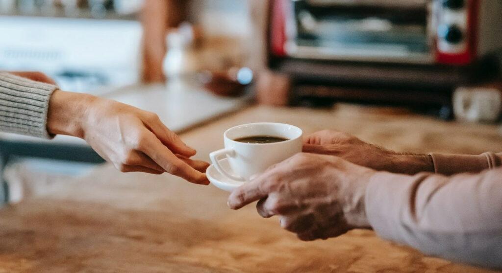 pessoa entregando uma xícara de café para outra.