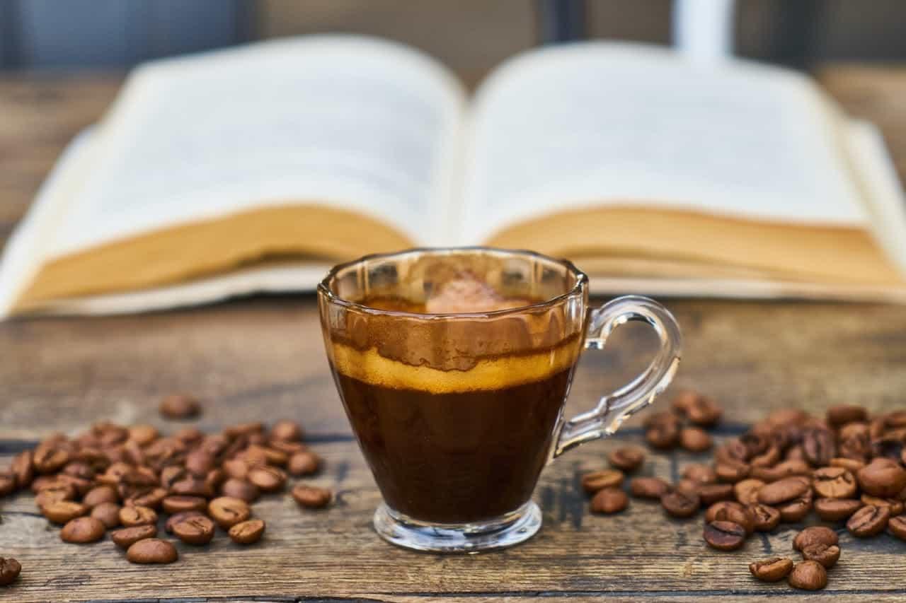 Xícara de café em cima de uma mesa com grãos de café em volta