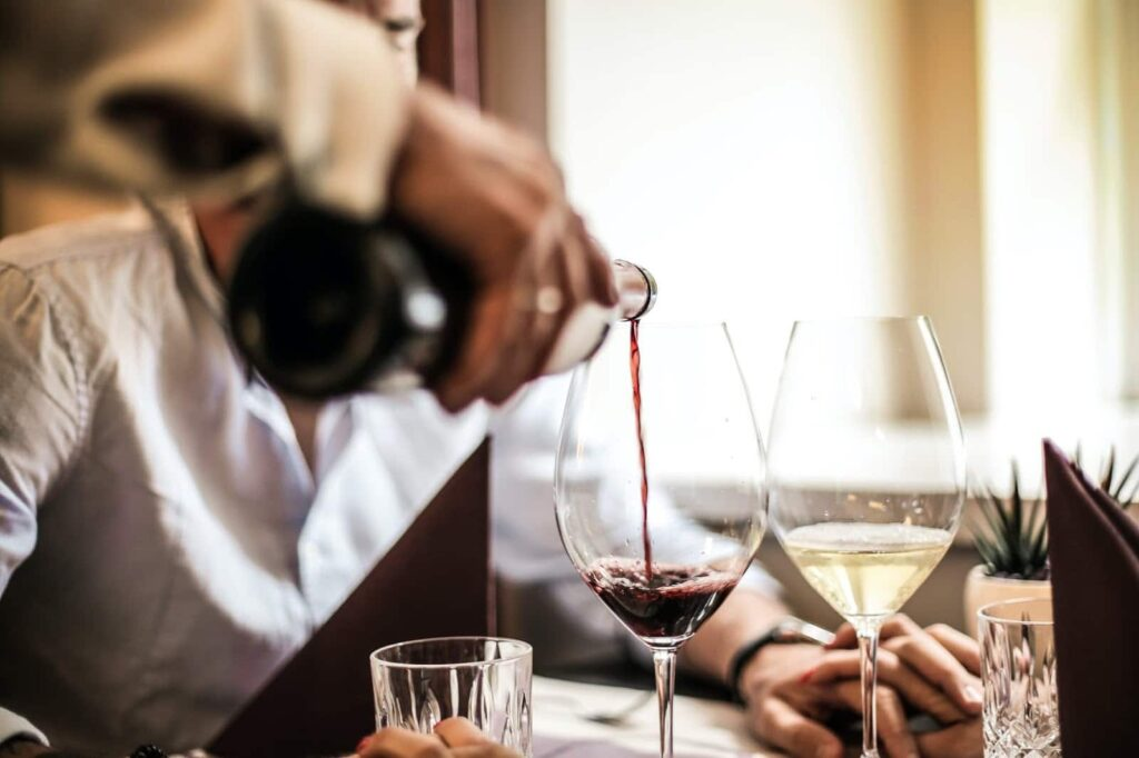 Pessoa servindo uma taça de vinho chileno.