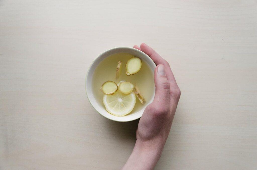 pessoa segurando uma xícarachá gelado com limão