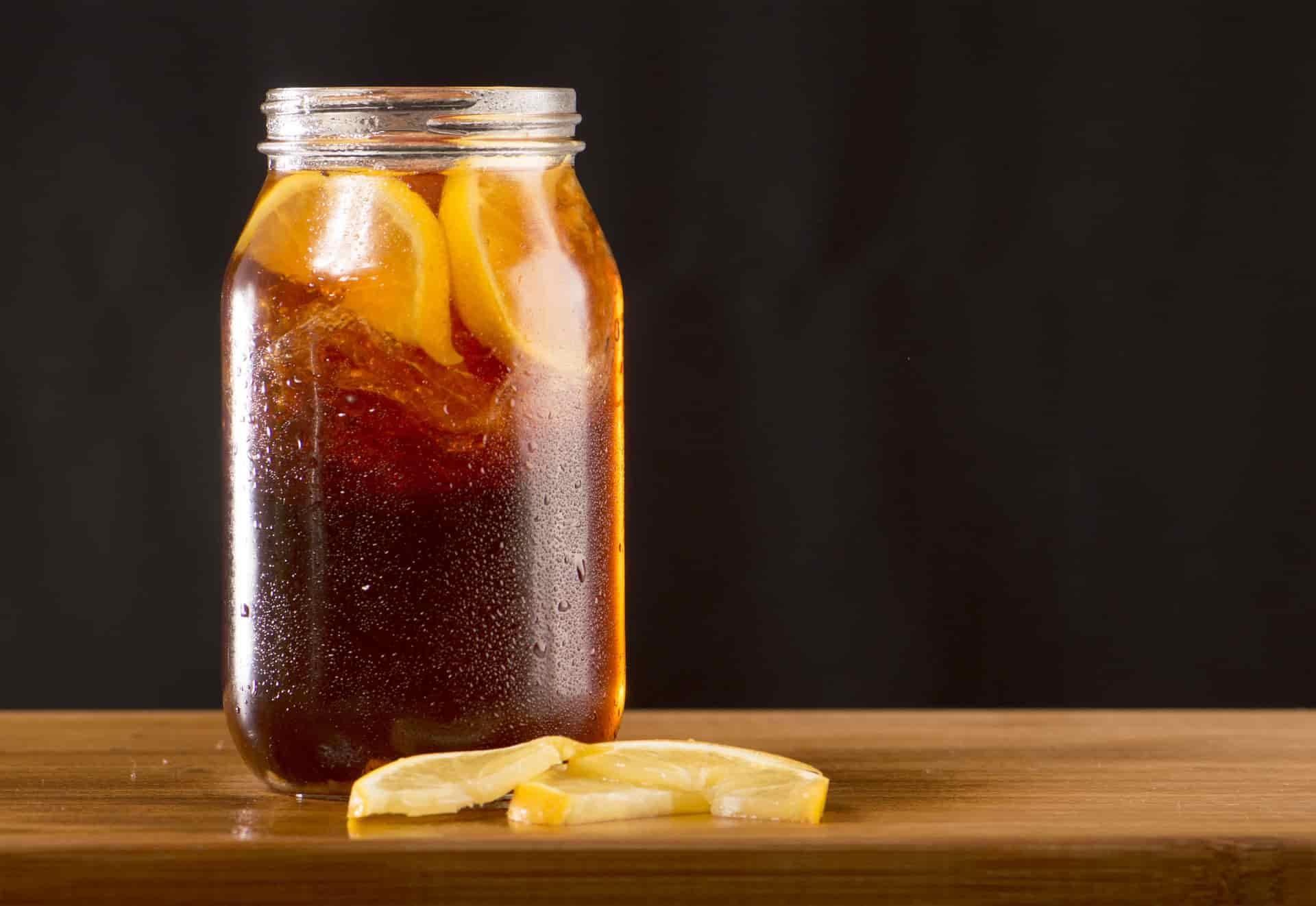 jarra de chá com rodelas de limão sobre a mesa