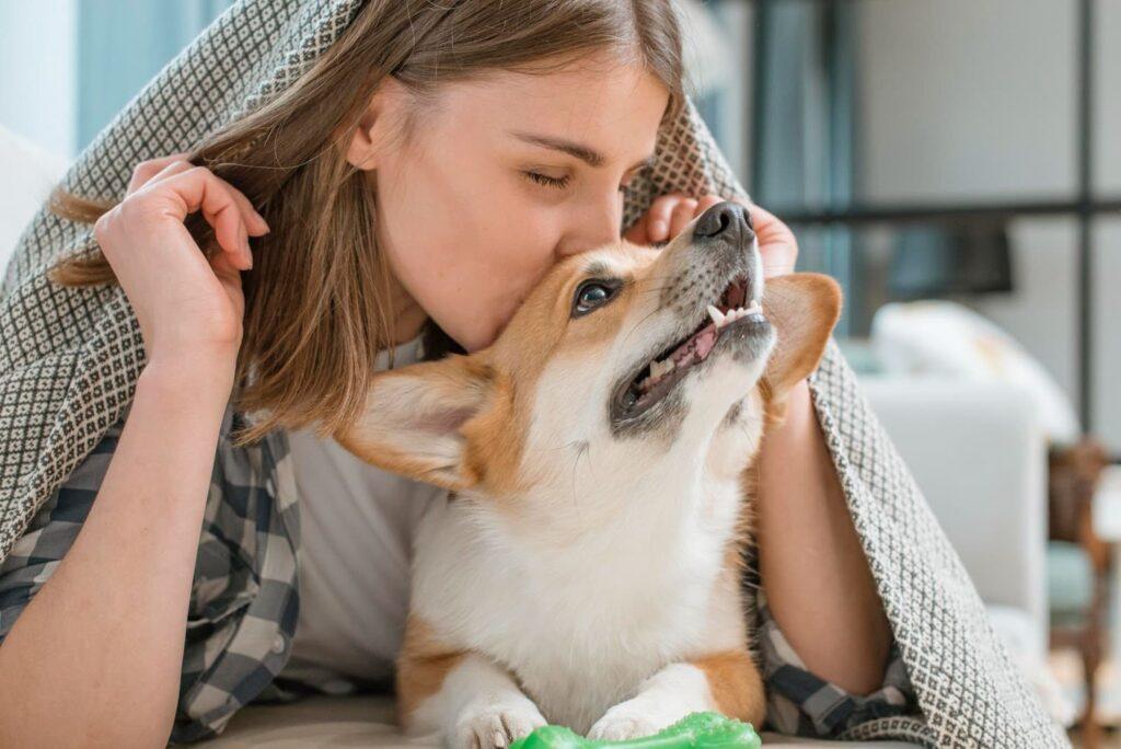 mulher beijando a cabeça de um cachorro.