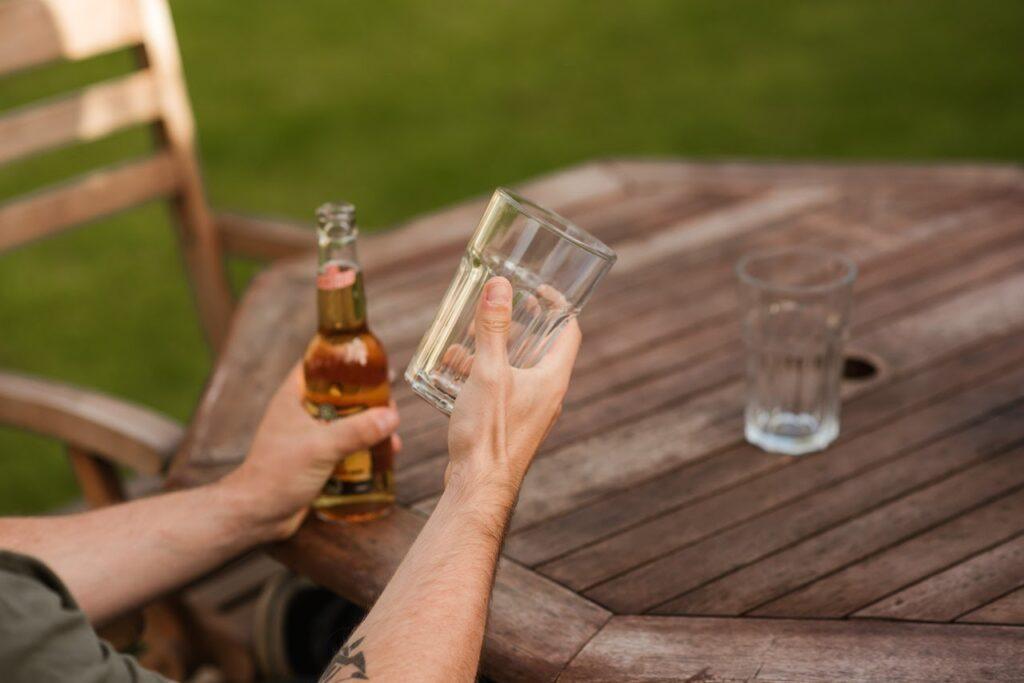 Na imagem temos uma pessoa servindo cerveja em um copo tumbler, apoiado em uma mesa de madeira.