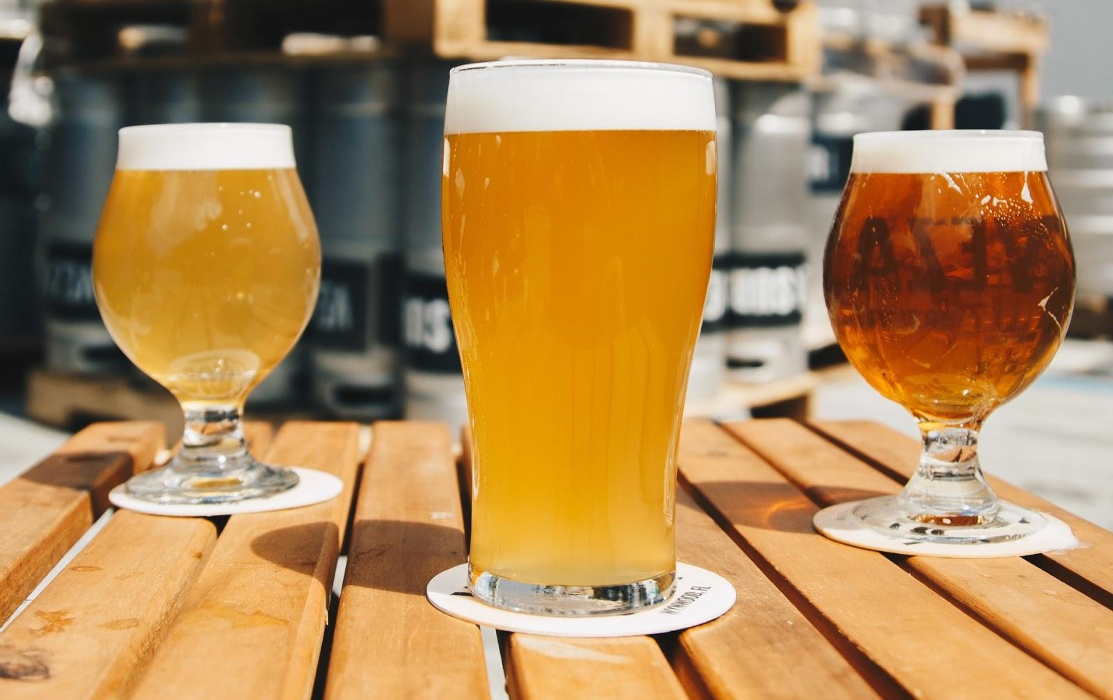 Na imagem temos dois dos tipos de copos para cerveja, em cima de uma mesa de madeira.